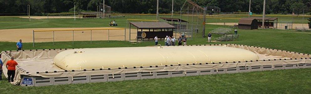 fuel bladder on portable secondary containment system for fuel spill prevention at a baseball field