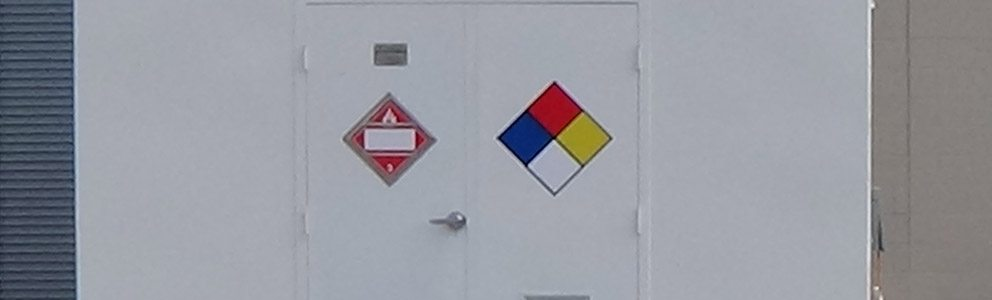 Doors of hazmat storage building marked with hazardous materials symbols
