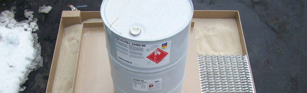 grease containment pad holding hazardous material barrel