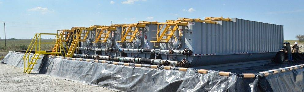 A row of five containment systems for hazardous material on poly dike secondary containment system