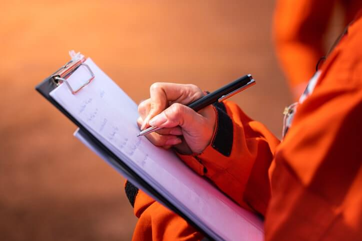 Worker writing on an EHS audit clipboard with a pen