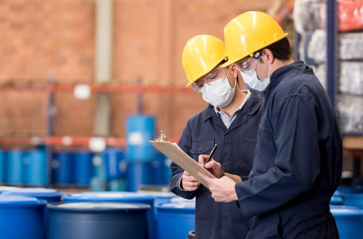 Two workers holding clipboards check OSHA chemical safety requirements
